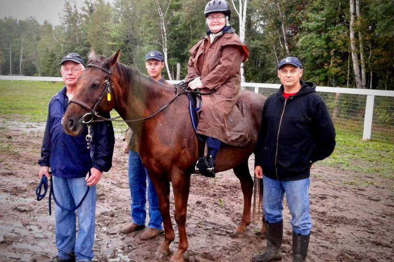 A woman on a horse with instructors standing on each side of the horse, everyones posing for the photo by looking at the camera