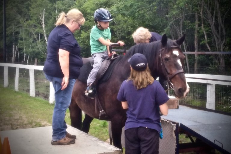 Four people in this image, one child on a horse and three instructors along side the child supervising the situation.