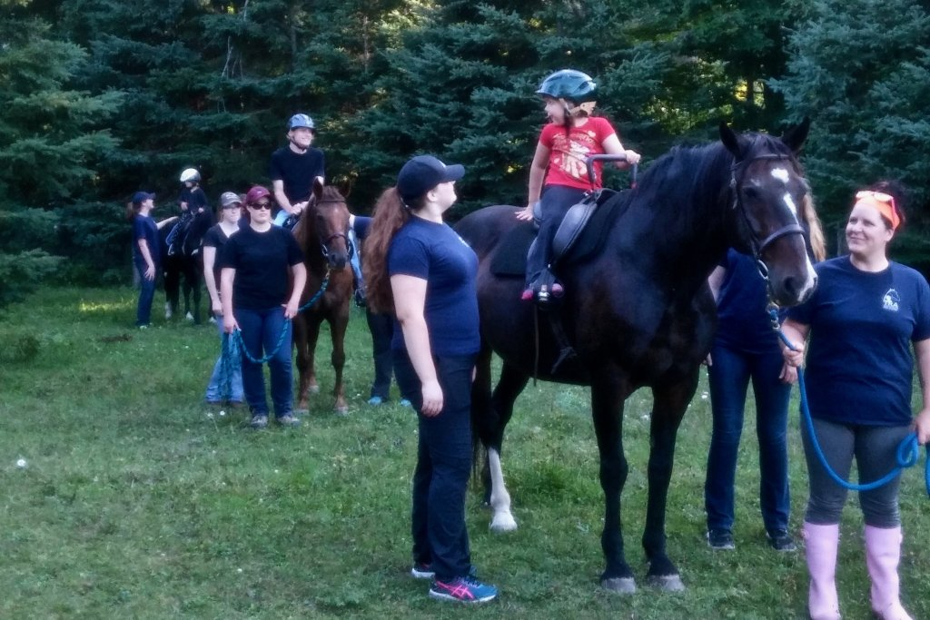 Shows a group of riding students, being lead by instructors. 2 lessons seem to be happening in the current scene.