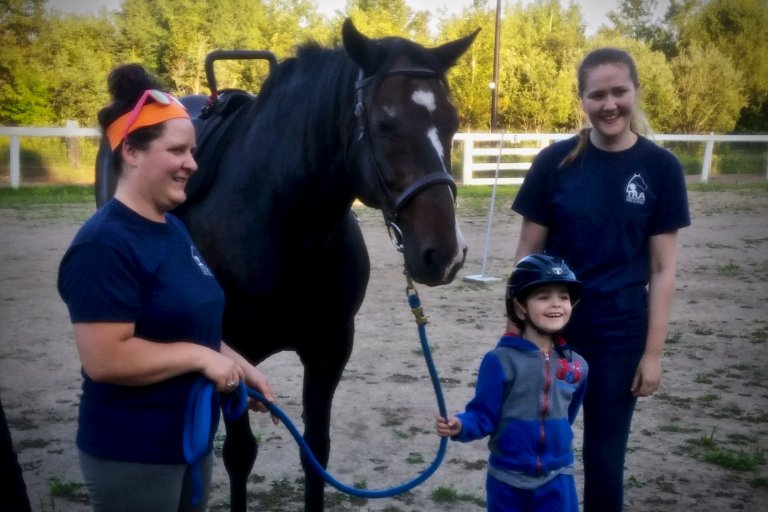 A young girl is holding onto the leash for the horse with an instructor holding onto the same leash. There is also another person behind the young child smiling.