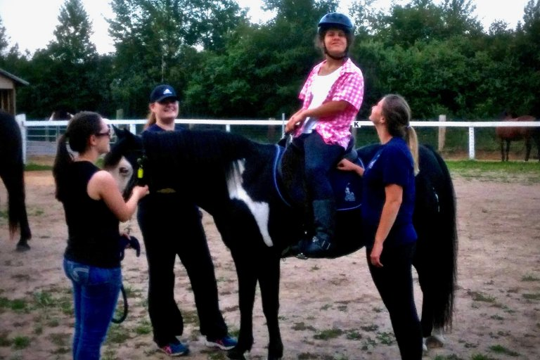 A woman in a pink shirt is riding a horse while three instructors supervise the situation.