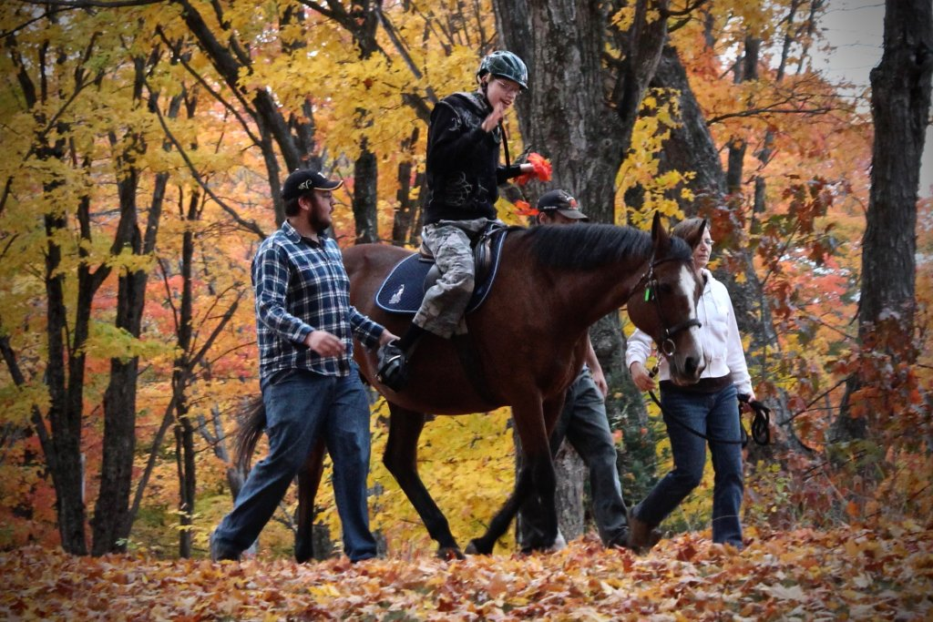 Boy riding a horse, while two volunteers are on the sides, helping to lead the horse through the forest