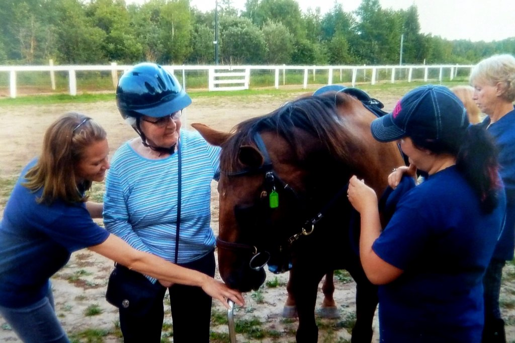 Three people petting a horse, one person is letting the horse smell the back of their hand. while the others are petting his beautiful mane