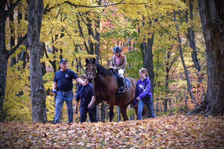 young girl riding a horse, while two volunteers are on the sides and an instructor is leading the horse through the forest
